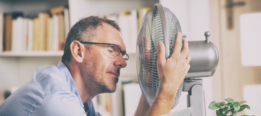 Image of man holding fan close to his face.