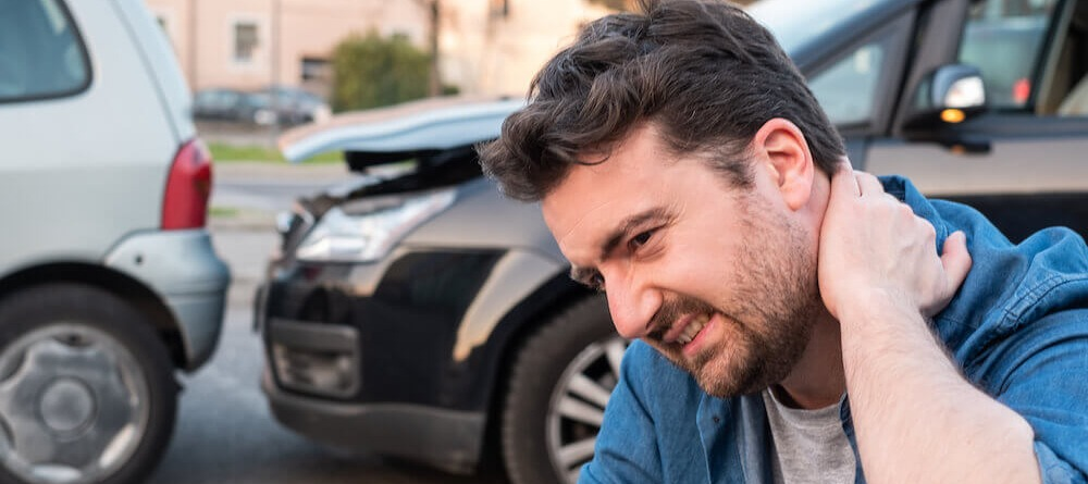 Man feeling pain in neck from car accident