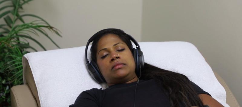 A woman at Cognitive FX lying down in a chair with headphones on.