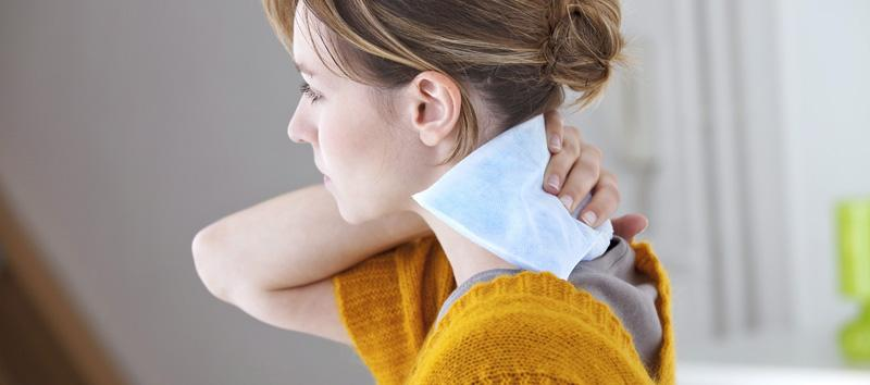 A woman holding a heating patch on her neck.