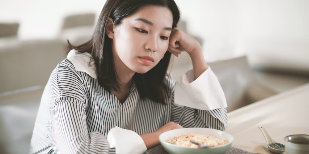 A woman is sitting down at the kitchen counter looking at a bowl of food.