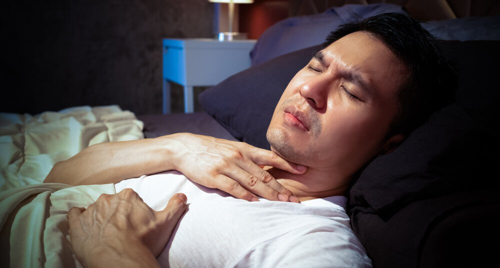 A man is lying down in bed grabbing his throat with pain from acid reflux.