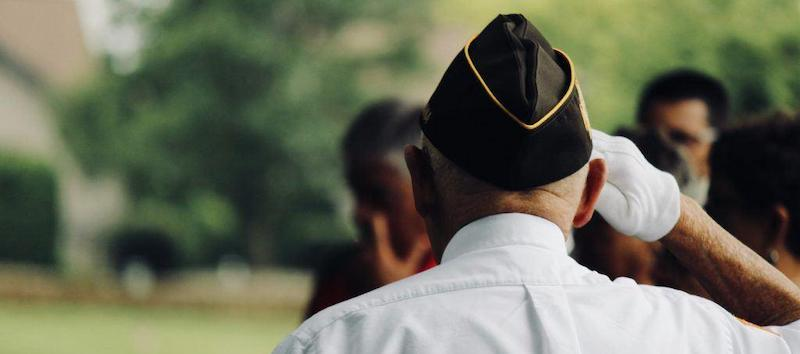 A photo of a veteran from behind wearing his hat while saluting.