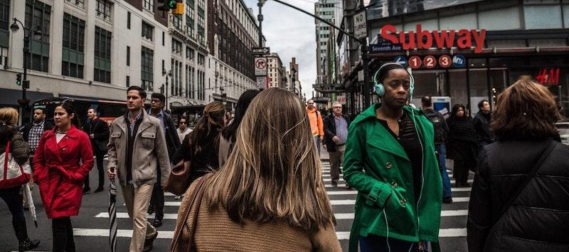 A photo of several people walking down a busy street in New York.
