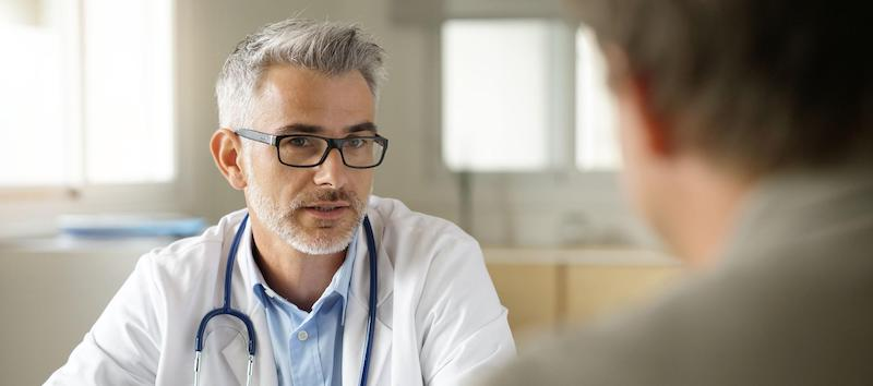 A doctor meets with a client to go over treatment options.