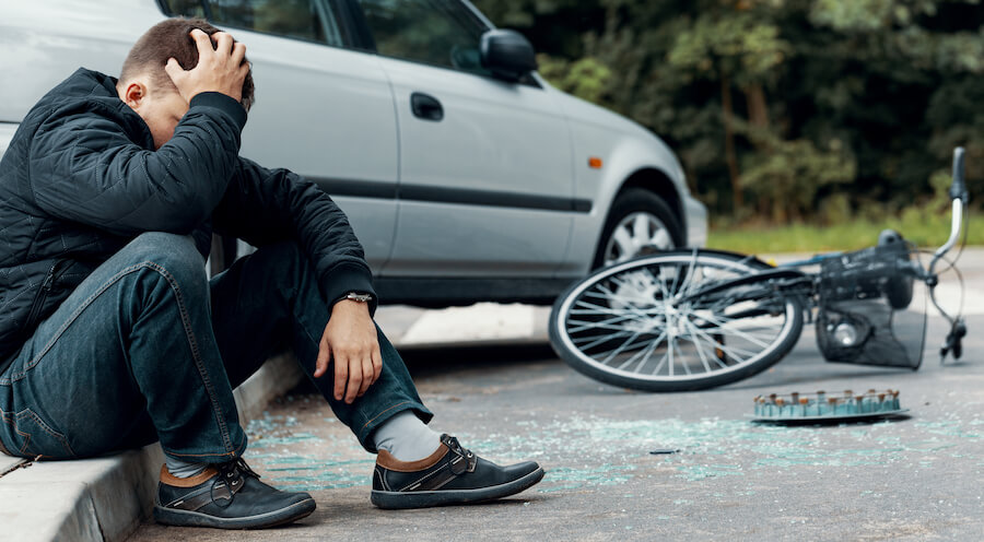 A photo of a man sitting on the ground after getting into an accident and hitting his head.