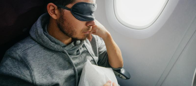 A man resting on the plane with an eye mask covering his eyes.