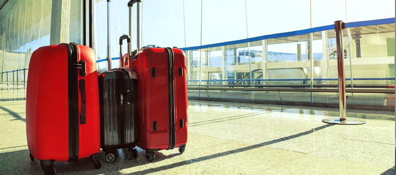 A photo with 3 rolling luggage bags (2 red and 1 black) at the airport.