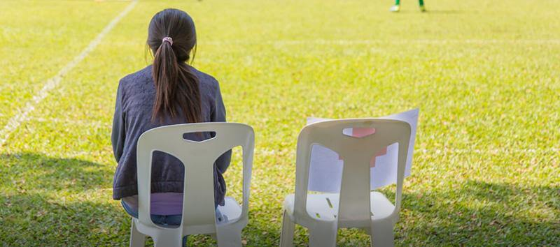 A woman is sitting in a chair watching a football game with an empty seat next to her.