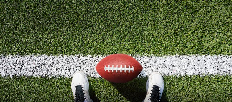 A picture of someone looking down at their feet on the sidelines with a football.