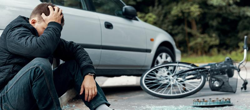 Man sitting next to his car and his bike, grabbing his head.