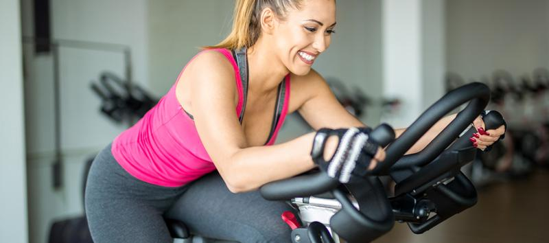 A young woman is smiling while riding a stationary bike.