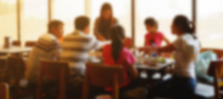 A blurry photo (overstimulated view) of a family sitting down at a table having a dinner