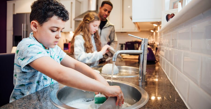 A dad is cleaning up the kitchen with his two kids washing the dishes