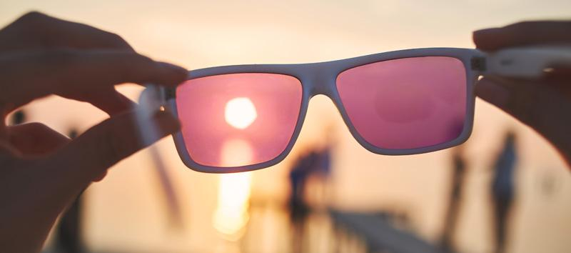 A photo of colored glasses as the sun is setting in the background.