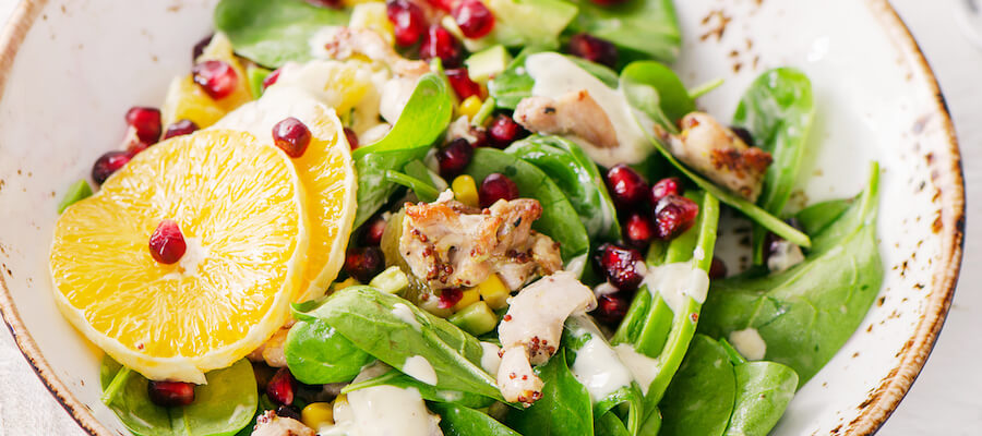 A photo of a fresh bowl of salad with pomegranate seeds, quinoa, orange slices, and chicken breast, served over spinach.