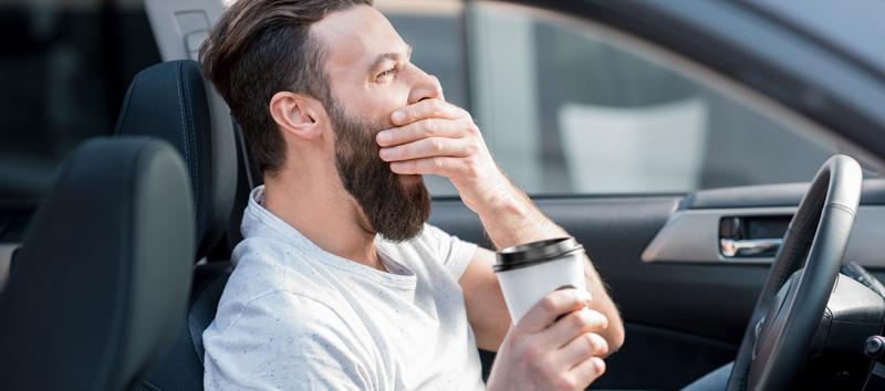 A man is parked in his car with a cup of coffee.