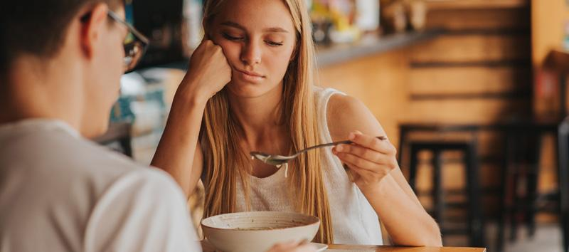 A young woman is sitting at a table staring down at her spoon.
