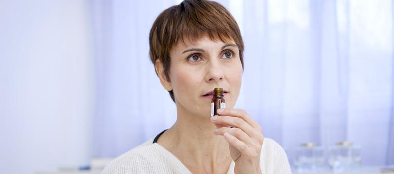 A woman with short and dark brown hair is smelling peppermint oil.