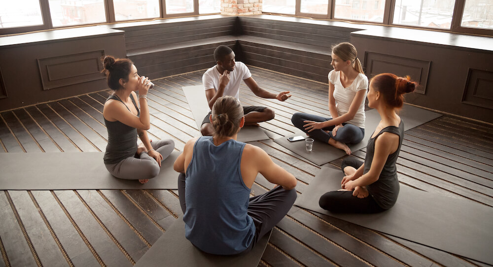 A group of 5 people sitting on the floor before their yoga class.