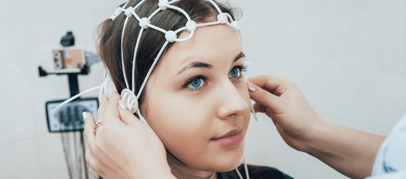 A photo of a woman getting ready for an EEG.