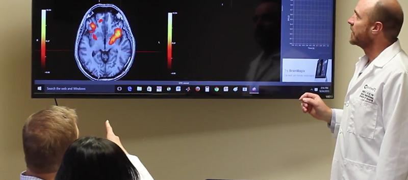 A doctor and his patient are looking over an fMRI.