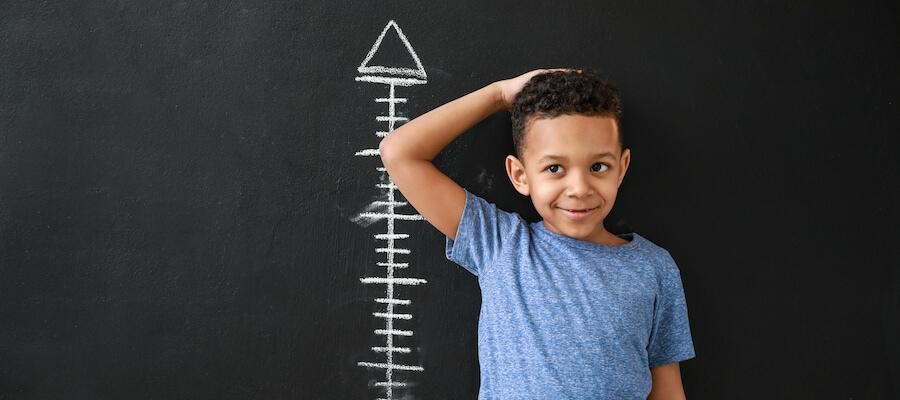 A young boy is standing against a wall to get his height taken.