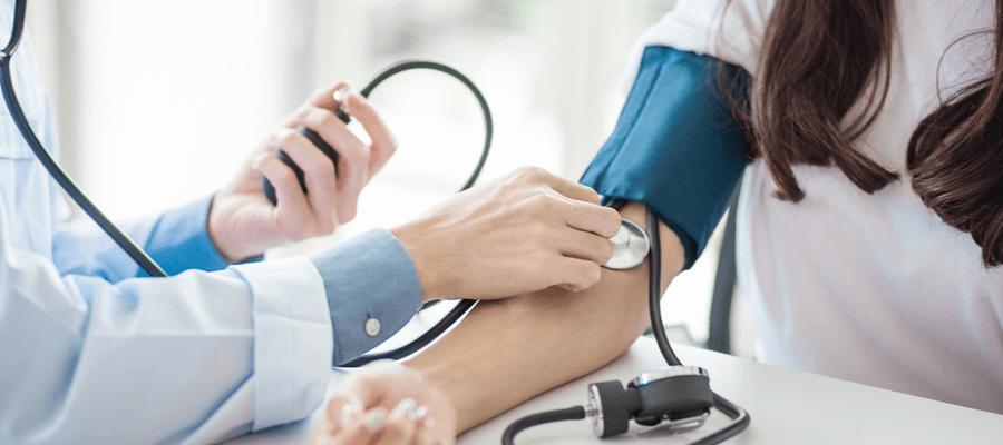 Doctor measures patient's blood pressure.