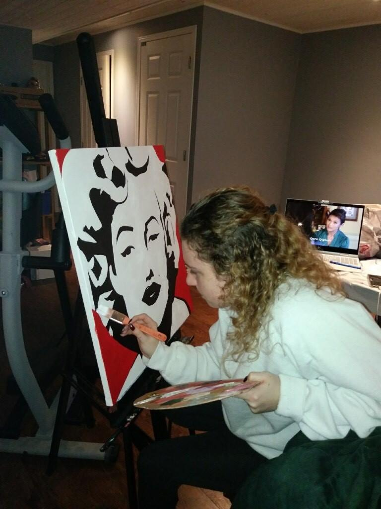 A photo of Sam painting an abstract Marilyn Monroe.