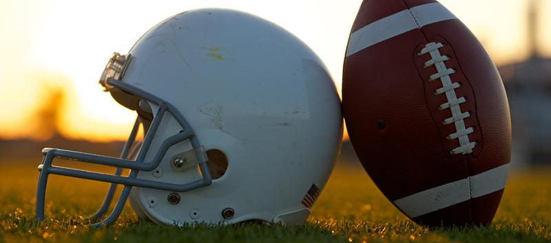 A football helmet sitting next to a football.