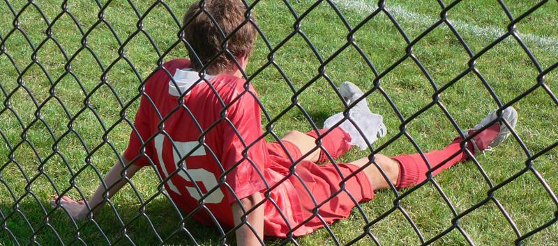A young boy is sitting on the field behind a fence wearing his jersey.