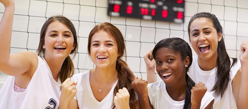 A group of 4 girls playing volleyball at school.