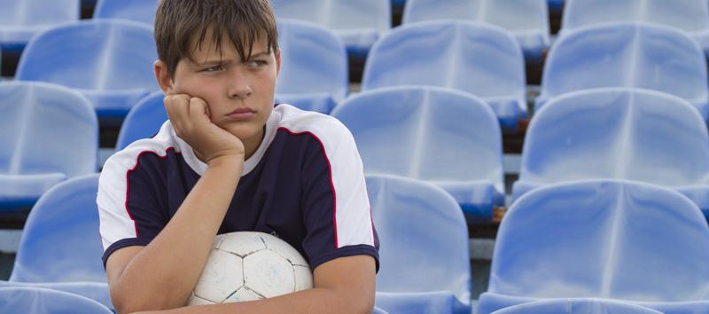 A young boy is sitting on the bleachers holding a soccer ball with his hand on his chin.