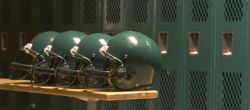 4 green football helmets in front of lockers in a locker room.