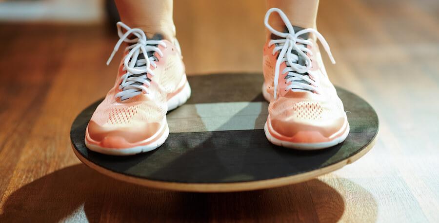 A woman balancing on a balance board.