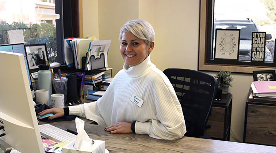 image of a woman sitting at a desk and smiling