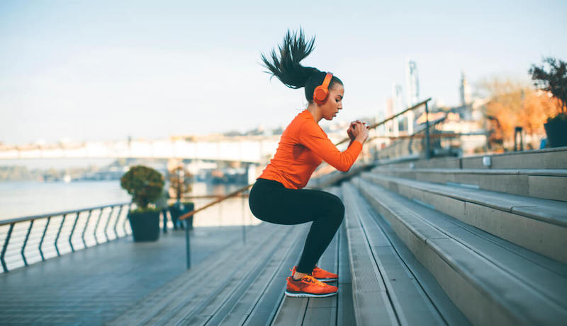 A woman is exercising on stairs.