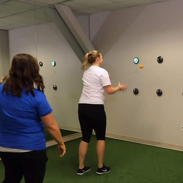 young woman exercising with a neuromusclar therapist at Cognitive FX